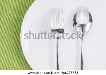 spoon and fork on white plate and green fabric