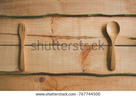 Spoon and fork wooden on table, Branch rose, for good food health and life
