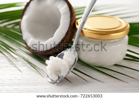 Spoon and jar with coconut oil on wooden table