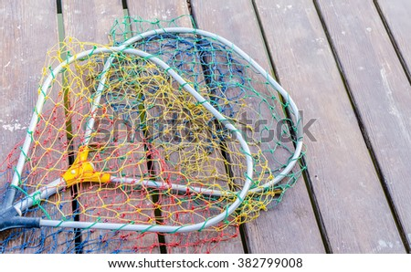 Spoon fishing net on a wooden table - stock photo