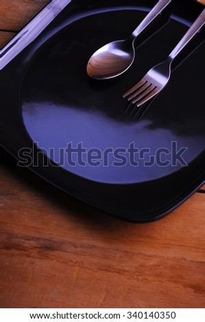 spoon, fork and black plate - stock photo