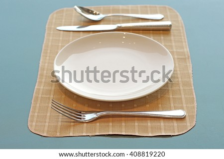 spoon fork  knife and empty white plate - stock photo