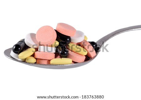 Spoon full of colorful pills on a white background - stock photo