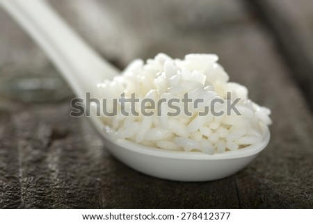 Spoon full of rice over wooden background