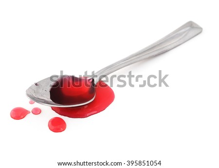 Spoon full of spilled medicine on a white background.