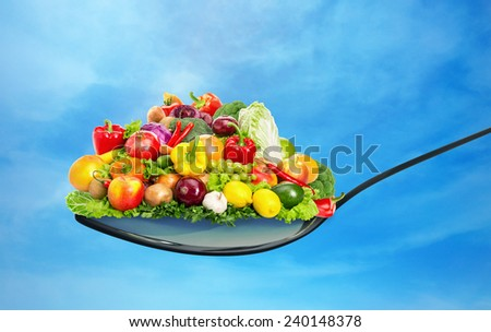 Spoon full of various fruit and vegetables - stock photo