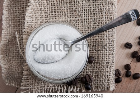 Spoon in a glass bowl of sugar, close up - stock photo