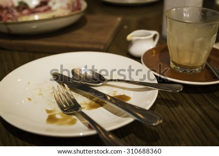 Spoon, knife and fork on dirty empty dessert plate. - stock photo
