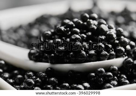 spoon of black caviar close-up in a heap of black caviar horizontal - stock photo