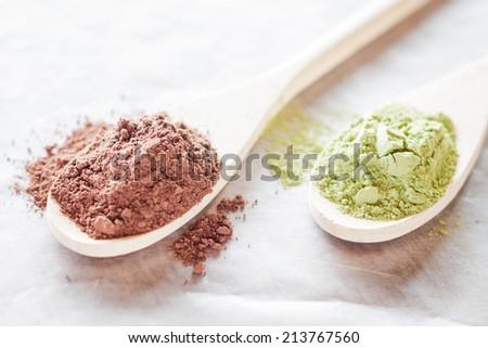 Spoon of cocoa and green tea powder - stock photo
