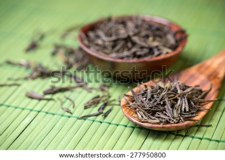 Spoon of dried green tea leaves - stock photo
