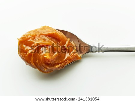 Spoon of melted caramel cream on a white background - stock photo