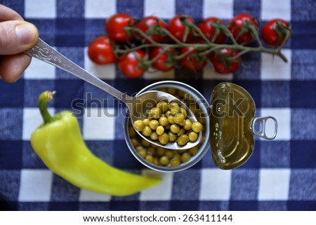 spoon of tinned green peas - stock photo