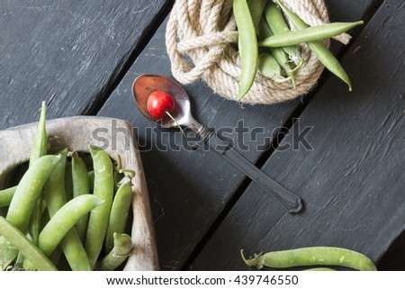 spoon with a cherry and green beans