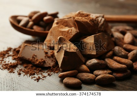 Spoon with aromatic cocoa and chocolate on wooden background, close up - stock photo