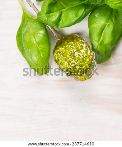 Spoon with Basil pesto and herbs leaves on white woooen background, top view - stock photo