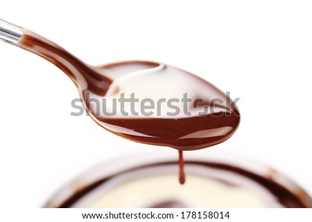 Spoon with chocolate cream. Isolated on a white background. - stock photo