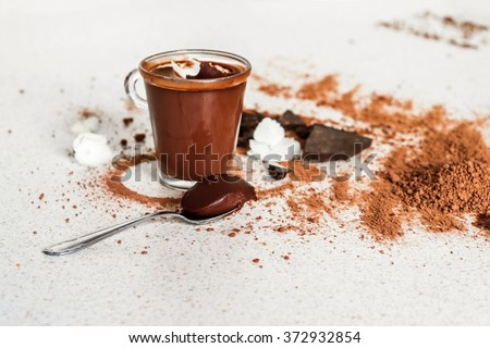 Spoon with chocolate mousse, on the background is glass with chocolate mousse, white table is sprinkled with cocoa powder and fragments of dark chocolate and flower - stock photo