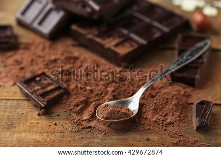 Spoon with cocoa powder and dark chocolate on table - stock photo