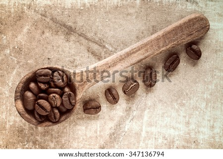 Spoon with coffee crop beans on dirty background - stock photo