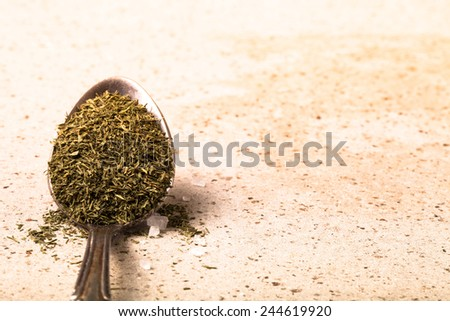 Spoon with dried herb and salt on the stone background. Toned. - stock photo
