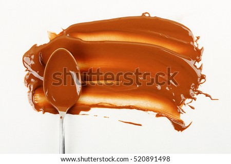 spoon with melted chocolate on baking paper