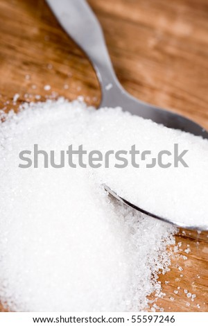 spoon with sugar closeup on wooden background - stock photo