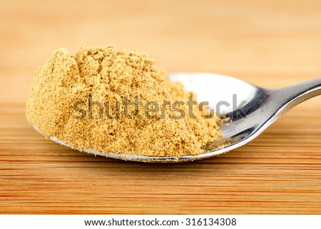 Spoonful of ground ginger powder - stock photo
