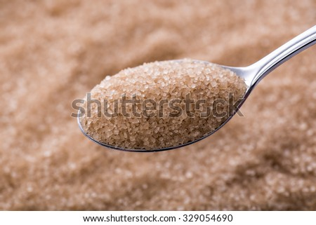 Spoonfuls of brown sugar cane on sugar background - stock photo