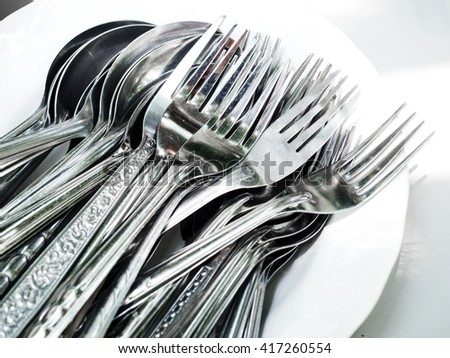 Spoons and forks on white plates - stock photo