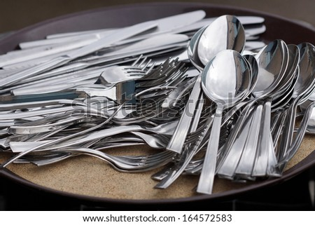 Spoons,forks and knives lying on a tray.