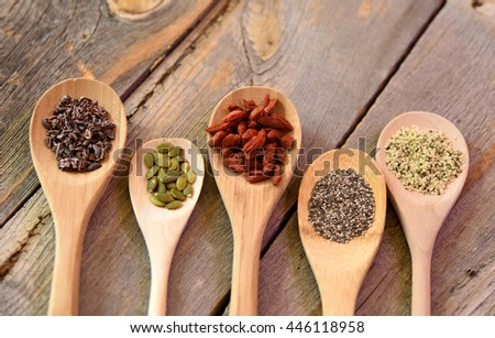 Spoons full of super foods on a rustic wooden table - stock photo