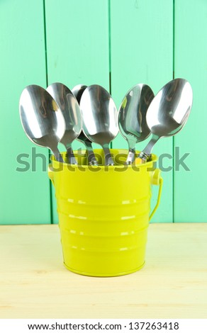 Spoons in metal bucket on color wooden background - stock photo