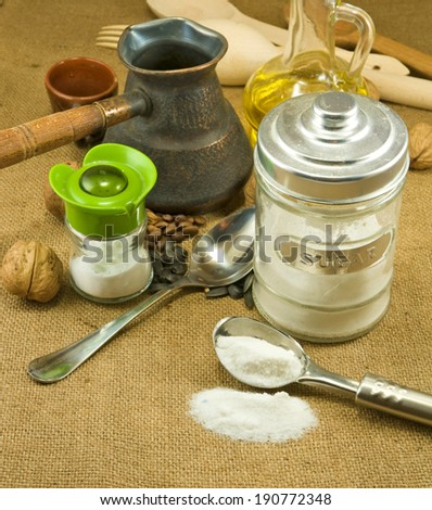 spoons, nuts, seeds,butter, salt shaker, coffee beans, a cup on a green background closeup - stock photo