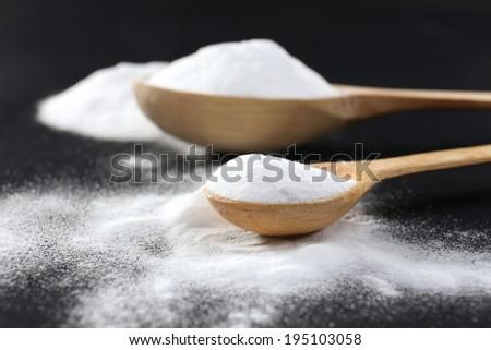 Spoons of baking soda on black background - stock photo