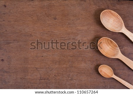 Spoons on oak wood table background - stock photo