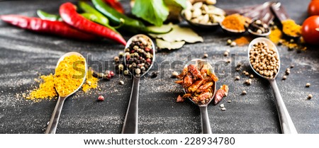 spoons with different spices and vegetables on a black table - stock photo