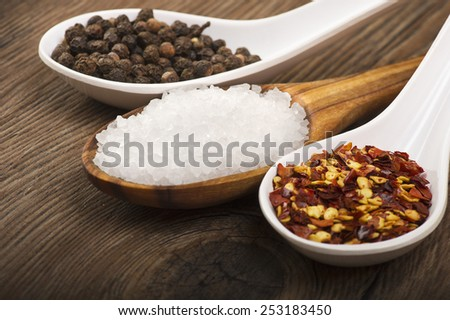 spoons with pepper, salt, chili pepper on wooden table  - stock photo