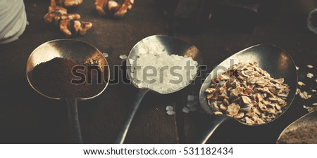 Spoons with sugar, coffee, oats and meringue, chocolate marshmallow, honey and nuts on a real brown wooden table. Christmas cake preparation.