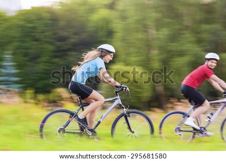 Sport and Bicycles Concept: Young Caucasian Couple Having a Speedy Bicycle Trip Outdoors. Blurred Motion Due to Paning.Horizontal Image - stock photo