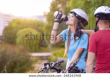 Sport and cycling Concept: Young Caucasian Cyclist Resting Together Outdoors. Having Water Break and Relaxing.Horizontal Image Orientation - stock photo