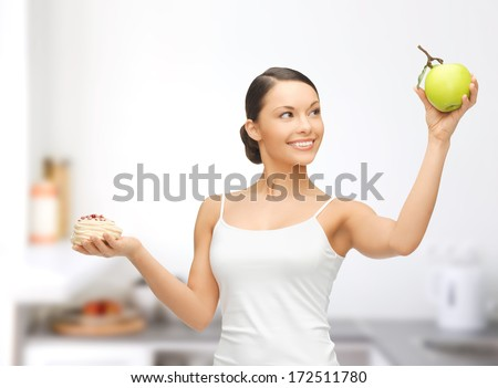 sport and diet concept - sporty woman with apple and cake in kitchen - stock photo