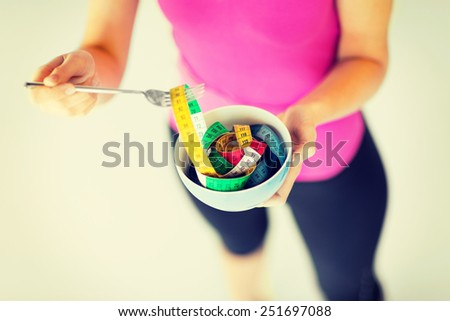 sport and diet concept - woman hands holding bowl with measuring tape - stock photo