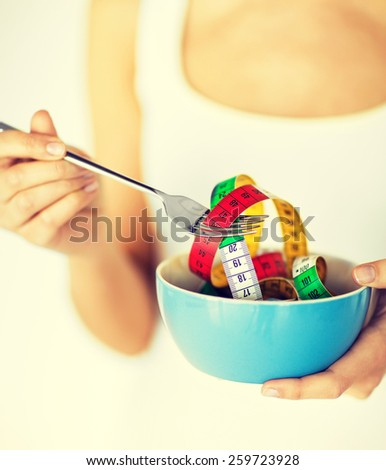 sport and diet concept - woman hands holding bowl with measuring tape