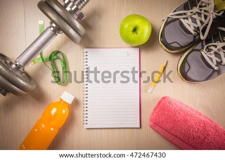 Sport and fitness objects and space notepad on wooden background