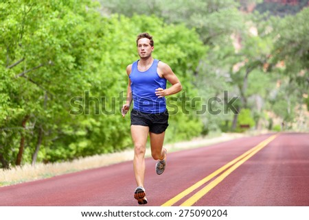 Sport and fitness runner man running on road training for marathon run doing high intensity interval training sprint workout outdoors in summer. Male athlete sports model fit and healthy aspirations. - stock photo