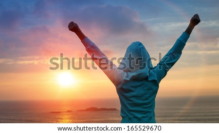 Sport and life achievements and success concept. Rear view sporty girl raising arms towards beautiful glowing sunshine. - stock photo