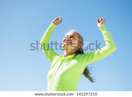 sport and lifestyle concept - woman runner celebrating victory - stock photo