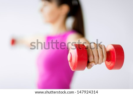 sport and recreation concept - sporty woman hands with light red dumbbells - stock photo