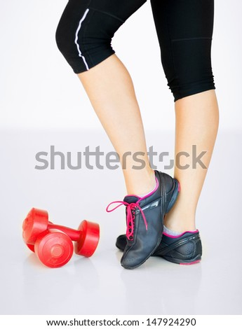 sport and recreation concept - sporty woman legs with light red dumbbells - stock photo